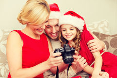Family in santa helper hats looking at pictires Stock Photo