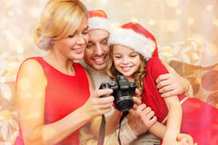 Family in santa helper hats looking at pictires Royalty Free Stock Image