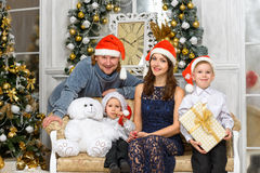 Family in santa helper hats with many x-mas gift boxes Stock Photo
