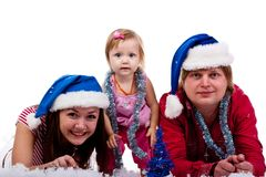 Family in Santa's hat lying in artificial snow Stock Photography