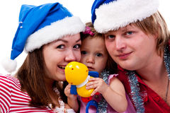 Family in Santa's hat sitting in artificial snow Royalty Free Stock Images