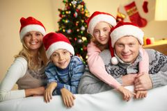 Family of Santas. Portrait of four happy family members in Santa caps looking at camera with smiles Stock Photography