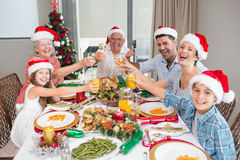 Family in santas hats toasting wine glasses at dining table Stock Photo