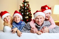 Family of Santas. Portrait of four happy family members in Santa caps looking at camera with smiles Royalty Free Stock Photography