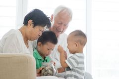 Family saving money and banking. Asian old people and children saving money at home. Family financial planning, investment, insurance, retirement, senior and Royalty Free Stock Photos