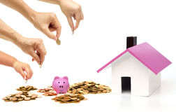 Family saving money  for buying a house. Grandmother, father, mother, and baby in the family do saving money in pink piggy banks for buying a house Royalty Free Stock Images