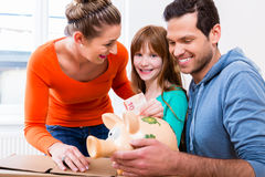 Family saving money by moving house. Putting bank note in piggybank royalty free stock images