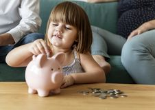 Family saving money in piggy bank Royalty Free Stock Photo