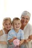 Family saving money in a piggybank. Smiling grandmother and children saving money in a piggybank royalty free stock image