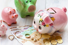 Family saving pigs Stock Images