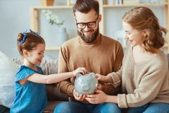 Family savings, budget planning, children`s pocket money. family with piggy Bank royalty free stock images