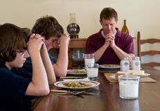 Family saying grace. Father and two boys saying grace at suppertime Royalty Free Stock Photos