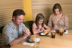 Family Saying Grace 2. A father, mother and daughter saying grace over a lunchtime meal Stock Image