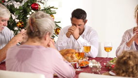 Family saying grace at the dinner table Stock Image