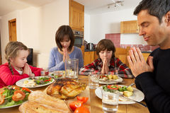 Family Saying Grace Before Eating Lunch. Together In Kitchen Stock Photos