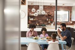 Family Saying Grace Before Meal Around Table At Home stock photos