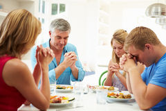 Family Saying Prayer Before Eating Meal At Home Together. Sitting Down At Table Stock Photo