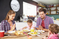Family Saying Prayer Before Eating Meal In Kitchen Together Stock Photos