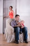 Family scene, father and son sitting in cozy. Armchair and feeding baby with bottle, mother entering the room, studio shot Royalty Free Stock Photo