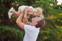 Family scene handsome young dad father posing playing with his baby daughter in central park forest summer meadow Happy life time Stock Image