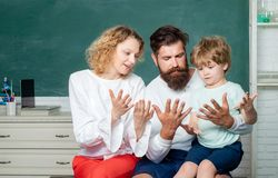 Family school. Woman and man helps the child boy Counting on fingers. Supporting pupils at school. Nice family photo of. Family school. Woman and men helps the royalty free stock photography