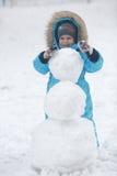 Family sculpts snowman Stock Photos