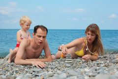 Family on sea coast build pyramid Royalty Free Stock Image