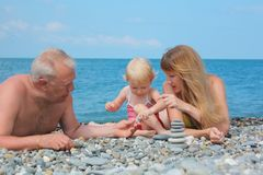 Family on sea coast and  pyramid of s Royalty Free Stock Images