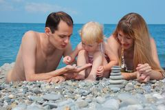 Family on sea coast and pyramid of stones Royalty Free Stock Photos