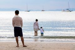 Family on the sea. A father watches his wife and son enter the water from the sandy beach stock images