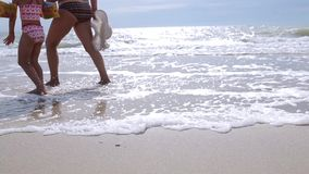 Woman with a little girl walking on the sea stock video footage