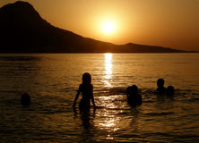 Family in sea at sunset. Family, father and children (group of people - best friends), playing, bathing, swimming -  enjoy at summer holiday at sunset on Royalty Free Stock Photography