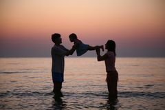 Family in sea on sunset stock photography