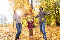 Happy family playing with autumn leaves at park Stock Photo