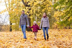 Happy family walking at autumn park Stock Images