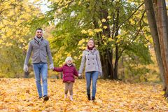 Happy family walking at autumn park stock photography
