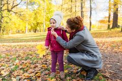Happy family with autumn leaves at park Royalty Free Stock Images