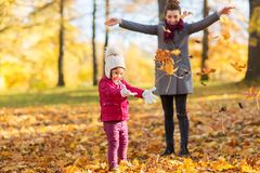 Happy family playing with autumn leaves at park Stock Images