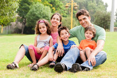 Family seated in park and smiling at camera Royalty Free Stock Photography