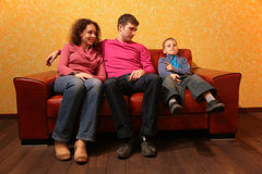 Family seating on red leather sofa royalty free stock image