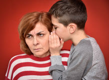 Family secret. Young boy whispering secret into ears of angry mother Stock Photography