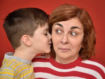 Family secret. Young boy whispering secret into ears of surprised mother Royalty Free Stock Photos