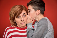 Family secret. Young boy whispering secret into ears of surprised mother Stock Photo