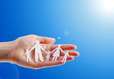 Family security. Paper family in hands  on blue sky Stock Photos