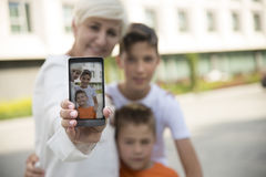 Family self shot. Mother with two sons taking a self portrait with smart phone Royalty Free Stock Images