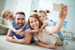 Family selfie. Happy young family taking selfie on the floor at home Stock Photography