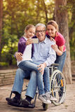 Family selfie time- granddaughter, daughter and disabled man in. Family selfie time in the park - granddaughter, daughter and disabled men in wheelchair Royalty Free Stock Images