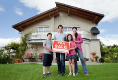 Family selling their home holding for sale sign Royalty Free Stock Photo