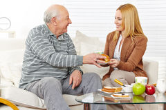 Family with senior citizen eating. Breakfast together at home stock photography