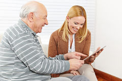 Family with senior citizen using. Happy family with senior citizen using a tablet computer stock photos